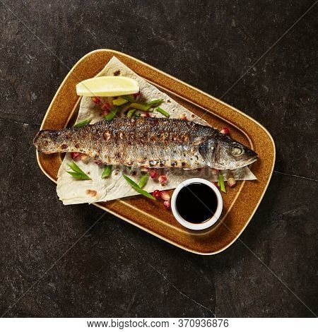 Grilled seabass with narsharab sauce top view. Suzuki fish served on brown plate. Delicious seafood dish. Tasty restaurant meal on marble table. Seasoned seafood overhead shot. Food preparing art