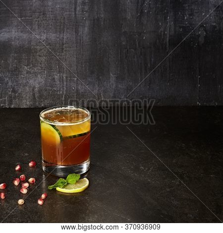 Seasoned cocktail with cucumber and apple. Alcohol drink on black table. Glassful of alcoholic concoction. Glass of booze. Mixed drink with spirits. Refreshing beverage with ice. Aperitif, soft drink