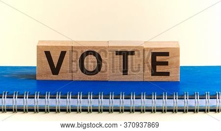 Vote Word Written On Wooden Blocks Black Font On Background Blu Notepad. Vote Word On Four Wood Cube