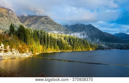 Capilano Lake Against A Snow-capped Mountain And A Stormy Cloudy Sky, The Forest On The Side Of The
