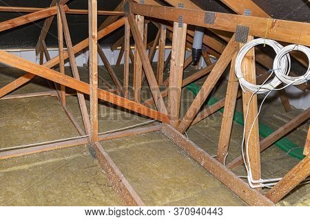 Ceiling And Attic Floor Insulation Made Of Rock Wool Between The Trusses, Visible Ends Of Plastic Pi