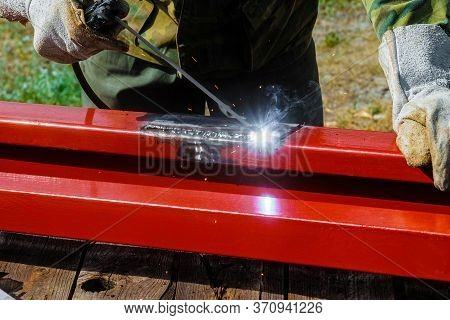 Welder Welds Steel Profile. Mounting Arc Welding Outdoors.