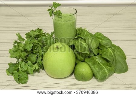 Green Smoothie On Light Wooden Background. Healthy Food Smoothie Veggies Cocktail. Green Vegetables