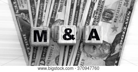 M & A (mergers And Acquisitions) - Word On Cubes Against The Background Of Dollar Bills. Business An