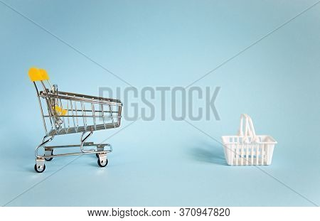 Concept Of Social Distance. Miniature Shopping Trolley And White Basket Isolated On Blue Background
