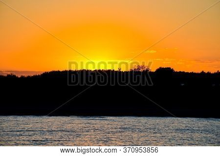 Bright Sunset Over The Lake. The Sun Has Set Behind The Forest. Yellow Sunset. Dark Water.