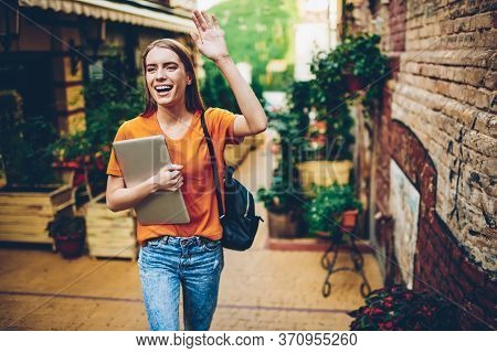 Happy Young Woman Strolling With Backpack And Laptop And Showing Hand To Friend For Meeting
