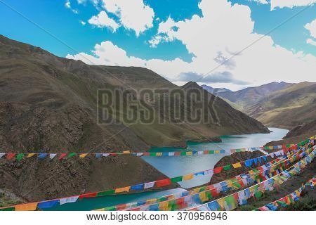 Mountain Holy Lake In Tibet With Prayer Flags- View From The Highway On The Way From Lhasa To Kailas