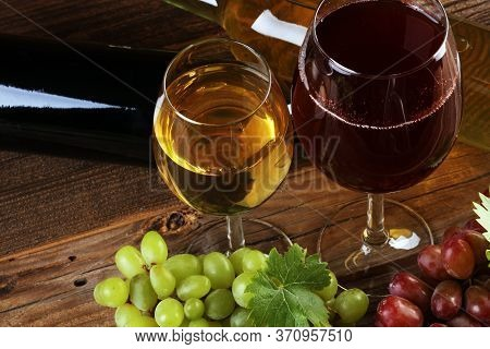 Red Wine And White Wine Glass With Grapes On Rustic Background
