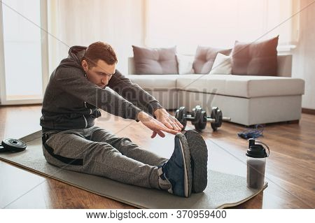 Young Ordinary Man Go In For Sport At Home. Beginner Or Amateur In Workout Activity Sit On Mat And S