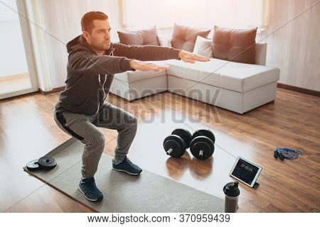 Young Ordinary Man Go In For Sport At Home. Real Picture Of Egular Guy Doing Squats With Stretch Han