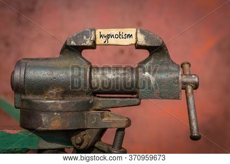 Concept Of Dealing With Problem. Vice Grip Tool Squeezing A Plank With The Word Hypnotism