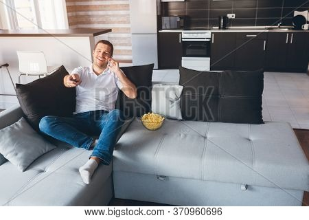 Young Man Watch Tv In His Own Apartment. Happy Excited Guy Talking On Phone And Using Remote Control