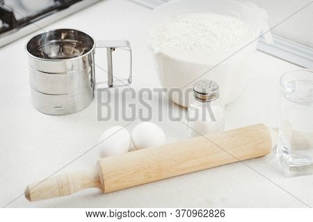 Flour, Eggs, Beater, Rolling Pin, Salt, A Glass Of Water And Eggshell White Table. Kitchen Table On