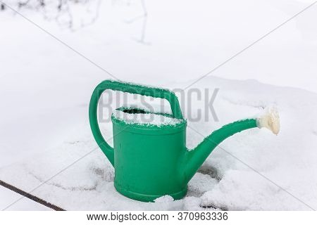 Snow, Frost, Snowflakes Are Falling. Watering Can Garden In The Snow In The Winter In The Garden. A