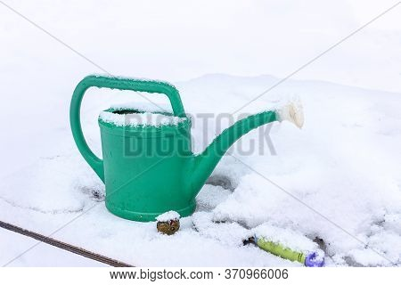Watering Can Garden In The Snow In The Winter In The Garden. A Snow-covered Garden Watering Can. Gar
