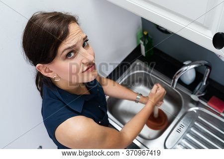 Cleaning Blocked Sink And Drain In Kitchen Using Plunger