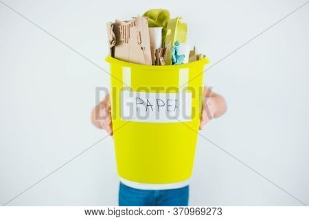 Young Man Isolated Over White Background. Guy Hold Yellow Plastic Bucket With Paper In It For Recycl