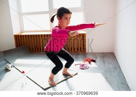 Little Girl Is Doing Squat Exercises Workout At Home. Cute Kid Is Training On A Mat Indoor. Little D