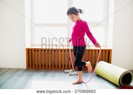 Little Girl Is Jumps On A Rope Workout At Home. Cute Kid Is Training On A Mat Indoor. Little Dark-ha