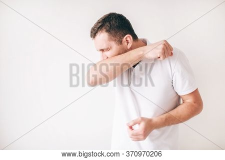 Young Sick Man Isolated Over White Background. Cough Out Loud And Cover Mouth With Elbow. Painful Co