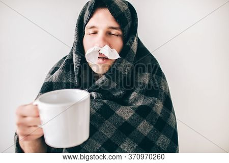 Young Sick Man Isolated Over White Background. Guy Covered With Blanket. Holding Cup Of Tea With Clo