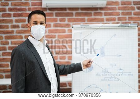 Business Man Giving Training Presentation In Office In Face Mask