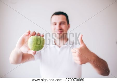 Young Man In White Shirt Isolated Over Background. Guy Hold Green Apple In Hand And Smile. Show Big