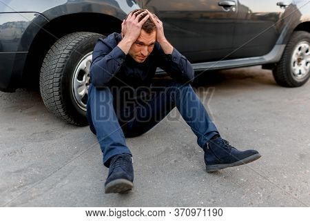Car Accident, Traffic Accident, A Man In Despair Sits Near The Wheel Of His Car. He Put His Hands On