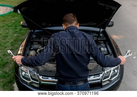 Car Breakdown Concept. The Car Will Not Start. The Young Man Is Trying To Fix Everything Himself. Th