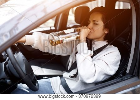 Drinking At The Wheel. A Drunk Woman Drives A Car. Life Threatening To Drink Alcohol And Drive A Car
