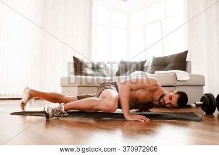 Young Man Go In For Sport At Home. Picture Of T-shirtless Guy Sportsman Doing Abs Exercising By Runn