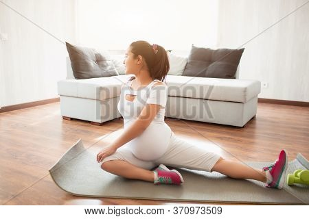 A Pregnant Woman Works Out On A Yoga Mat At Home. Pregnancy And Sports. Oga And Pilates For Pregnant