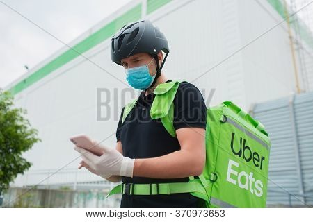 Kyiv, Ukraine - May 06, 2020: The Uber Eats Courier. The Food Delivery Man Uses A Smartphone To Reac