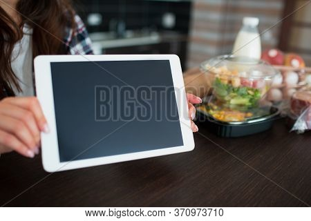 Food Delivery Concept. A Young Woman Orders Food Using A Laptop At Home. On The Table Are Milk, Sala