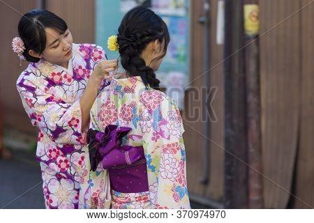 Kyoto, Japan - November, 8, 2019: Females In Traditional Japanese Geisha's Kimono Making Hairdo On S
