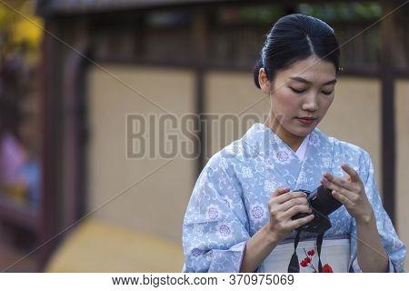 Kyoto, Japan - November, 8, 2019: Beautiful Tranquil Japanese Girl Posing In Geisha Kimono With Phot