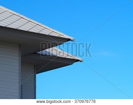 House With Blue Sky Background.copy Space.slate Roof And Slope With Clouds And Blue Sky Background.t