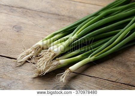 Fresh Green Spring Onions On Wooden Table, Closeup