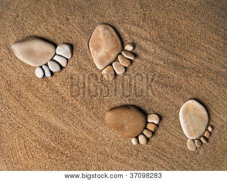 trace feet steps made of a pebble stone on the sea sand backdrop