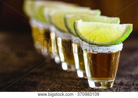 Several Glasses Of Tequila Lined Up, A Drink Of Mexican Culture, Made Of Distilled Alcohol, Lemon, S