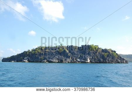 Limestone Rock Formation With Sands, Trees, And Blue Water Sea In Coron, Palawan, Philippines