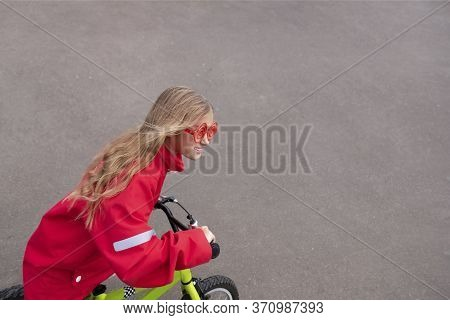 Young Blonde Girl In Red Jacket Riding Bike. Child Bicycle In City. Little Lady Enjoying Bike Ride O