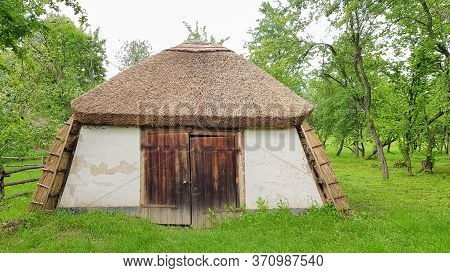 Ukraine, Kiev - June 11, 2020. Old Peasant Ukrainian House Or Barn In The Summer With A Thatched Roo