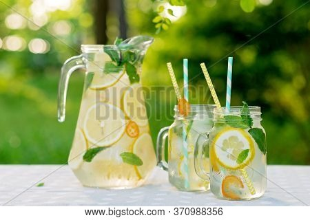Lemonade Refreshing Drink In A Jug And Jars With Lemons, Fresh Mint And Ice On A Garden Table. Summe