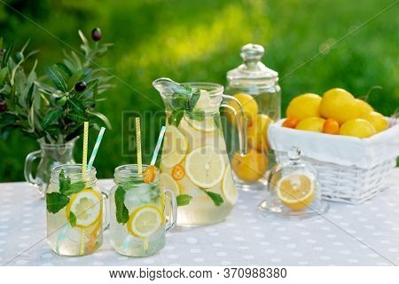 Lemonade Refreshing Drink In A Jug And Jars With Lemons, Fresh Mint And Ice With A Basket With Lemon