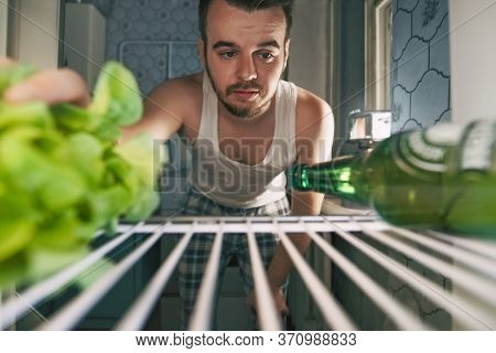 View From Fridge Man Chooses Vegetables Over Beer. Healthy Food Dilemma Young Caucasian Man With Bea