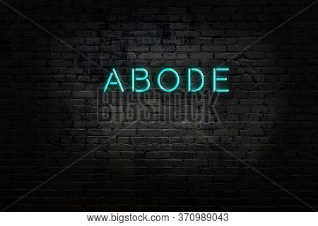 Neon Sign With Inscription Abode Against Brick Wall. Night View