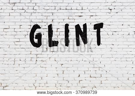 Word Glint Written With Black Paint On White Brick Wall.