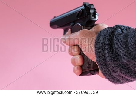 Gun in man hand on pink background